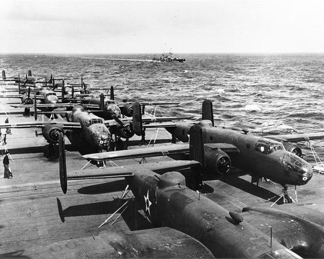 B-25 bombers on the flight deck of the USS Hornet en route to the mission's launching point for the Tokyo Raid. One of the escorting cruisers, the USS Nashville, is seen in the distance. (U.S. Navy photo)