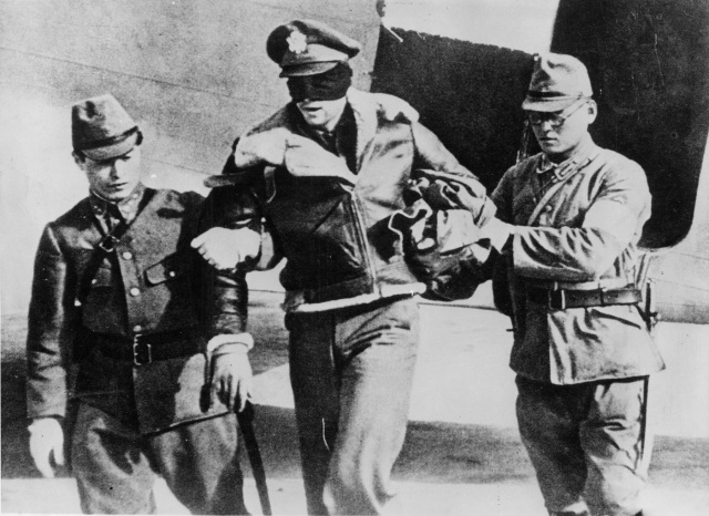 "U.S. Army Air Force Lt. Robert L. Hite, blindfolded by his captors, is led from a Japanese transport plane after he and seven other flyers were flown from Shanghai to Tokyo. Hite was co-pilot of crew 16, 34th Bomb Squadron, of the ""Doolittle Raiders"".  After 45 days in Japan, all eight were returned to China by ship and imprisoned in Shanghai.  On 15 October 1942 three were executed, one died in captivity. The four others, including Hite, were eventually liberated on 20 August 1945.  (U.S. Air Force photo)  Today, Lt. Col. Hite is one of only four surviving Tokyo Raiders."