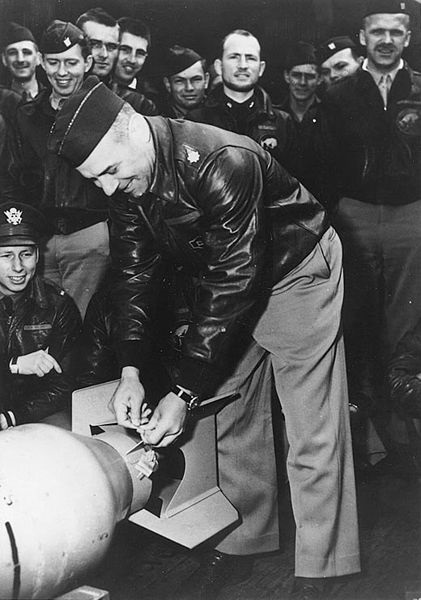"Lieutenant Colonel James H. Doolittle, USAAF  Wires a Japanese ""friendship""medal to a bomb, for ""return"" to its originators in the first U.S. air raid on the Japanese Home Islands, April 1942. Photographed on board the USS Hornet, shortly before B-25 bombers were launched to attack Japan. U.S. Naval History & Heritage Command Photograph"