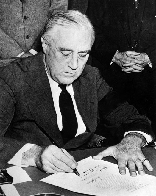 President Roosevelt signing the declaration of war against Japan on December 8, 1941 in the wake of the attack on Pearl Harbor. (National Archives and Records Administration - Abbie Rowe) (National Archives and Records Administration