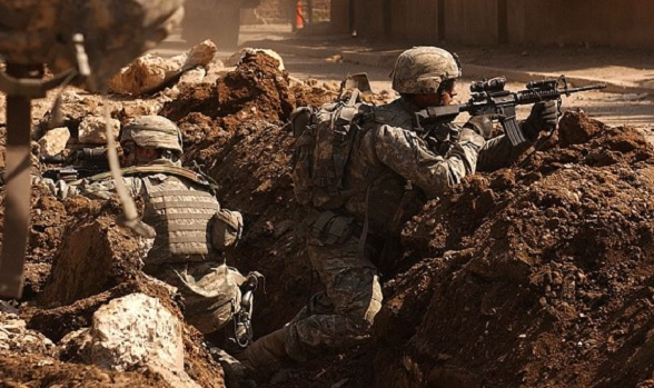 Sgt. Auralie Suarez and Private Brett Mansink take cover during a firefight with guerrilla forces in the Al Doura section of Baghdad on 7th of March 2007. The soldiers are from Company C, 5th Battalion, 20th Infantry Regiment, 3rd Brigade Combat Team, 2nd Infantry Division.