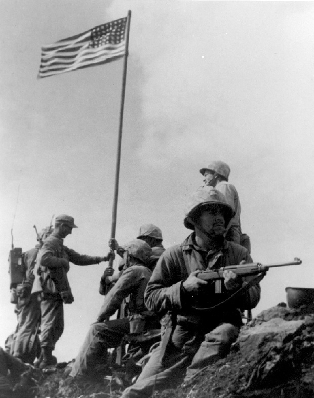 "Raising the First Flag on Mt. Suribachi, Iwo Jima Left to right: 1st Lt. Harold Schrier[7] (crouched behind radioman's legs), Pfc. Raymond Jacobs (radioman reassigned from F Company), Sgt. Henry ""Hank"" Hansen (cloth cap, securing flag pipe with left hand), Platoon Sgt. Ernest ""Boots"" Thomas (seated), Pvt. Phil Ward (helmeted, securing flag pipe with both hands), PhM2c John Bradley, USN (helmeted, securing the flag pipe with right hand, standing above Ward), Pfc. James Michels (holding M1 Carbine), and Cpl. Charles W. Lindberg (standing above Michels). Photo by by SSgt. Louis R. Lowery, USMC"
