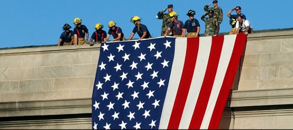 Firefighters and soldiers unfurl a large American flag over the side of the Pentagon during rescue and recovery efforts.