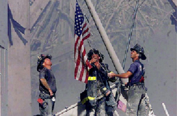 Firemen raise the flag at ground zero following the attack on September 11, 2001.