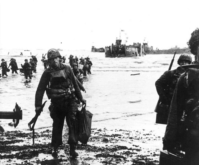 U.S. assault troops carrying equipment move onto Utah Beach. Landing craft seen in the background